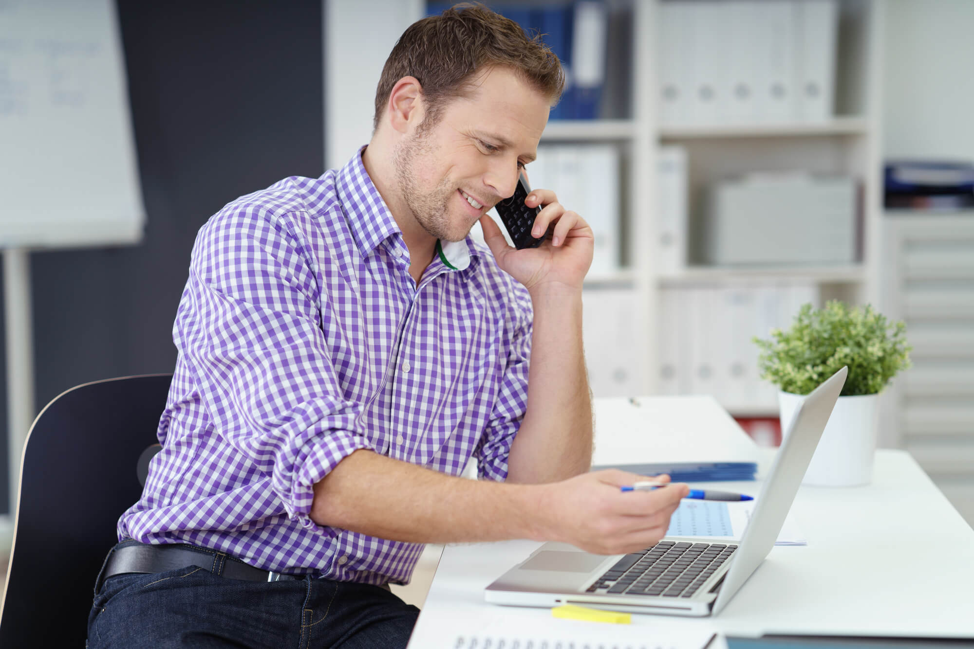 Man on phone with computer